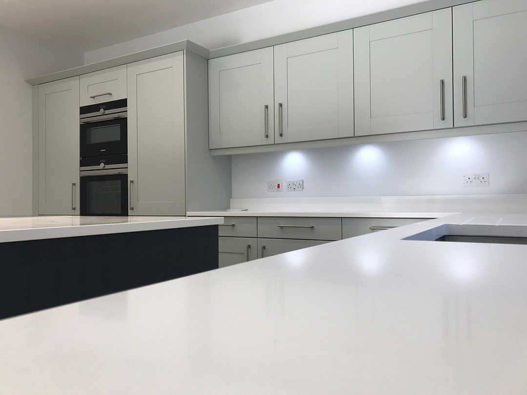 Kitchen design featuring 20mm Bianco Assoluto Quartz with Broadoak Shaker kitchen in Partridge Grey and a contrasting Charcoal.